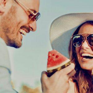 Α happy couple eating watermelon and having fun together.